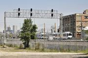 Light-rail trains run by the old Gates plant.