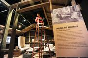 Bill Lecaine of AVI SPL installs motion sensors and speakers in a display at the History Colorado Center.