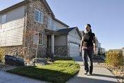 Judy Ferrel, sales associate at Richmond American Homes, walks past model homes in the Wheatlands development in Aurora.