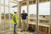 Tom Morton (blue shirt), a senior vice president at Brookfield Residential Colorado, talks with construction manager Jim Sanford at the first home to be built at the Midtown development.