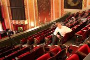 """Kyle Zeppelin, 39, principal of Zeppelin Development Inc., prepares for his photo in the balcony of the Paramount. His favorite movie is """"The Godfather."""" The film is sort of a metaphor for a family business, says Zeppelin, for the different personalities, relationships and characters. He says he also subscribes to the character Michael Corleone's theory of taking the business to the next level — minus the gangster element, of course."""