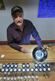Terry Hobbs , employee at the The Kind Room on South Broadway, moves marijuana under a magnifying light. The light is used by customers to look for impurities.November 2012