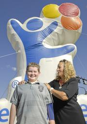 Lisa Schomp, owner of Schomp Automotive, with Nate Sheets, 13, Children's Hospital Colorado ambassador. Schomp is a supporter of the hospital. Schomp is the Outstanding Women in Business winner for Large Business Owners.