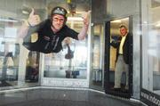 Bob Burke, Managing Partner at Indoor Skydiving in Lone Tree, stands in the doorway as instructor Josh Evans shows his technique. September 2011