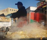 Francisco Sanchez makes sausage and onions for Good Ol' Burgers at the National Western Stock Show.