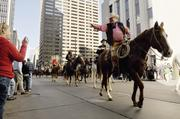 A horseman waves to the crowd during the National Western Stock Show parade in downtown Denver.January 2012
