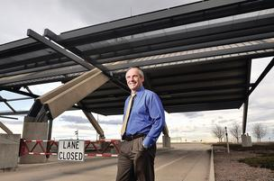 Stan Koniz, CFO of the E-470 Public Highway Authority, stands outside Plaza B on the highway between East Quincy Avenue and East Jewell Avenue. Five toll plazas have been empty since June 2009, when E-470 converted to a cashless, electronic tolling system.