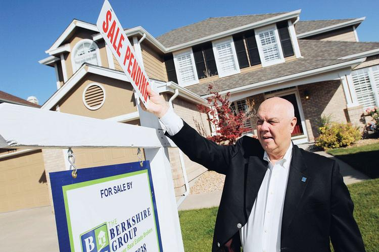 "Larry McGee, managing broker at The Berkshire Group, places a ""sale pending"" sign at a home in Highlands Ranch. The home was on the market for about two weeks before it went under contract."