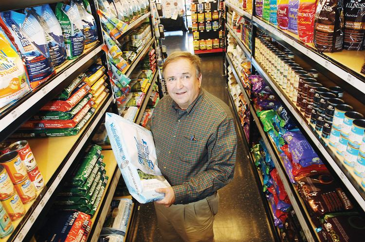 Bob Hartzell, president and CEO of Chuck & Don's Pet Food Outlet, shows a bag of premium dog food at the Cherry Creek store, which opened in January.