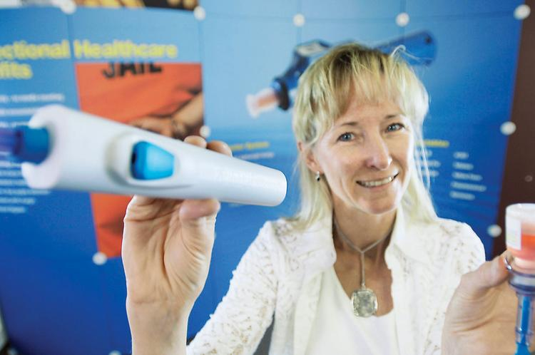 Heather Callender-Potters of PharmaJet displays the company's needle-less injector for vaccinations.