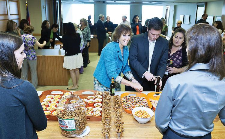 """Connie Purdy (center), a legal secretary at Wheeler Trigg O'Donnell, enjoys a """"flash party"""" for employees. These are spur-of-the-moment celebrations announced via email right when they happen."""