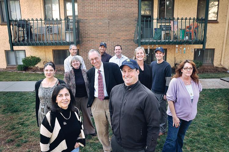 Aaron Miripol, president of the Urban Land Conservancy, stands in the middle (cap and black jacket) of a team effort for keeping affordable housing at a transit-oriented development. They are at the Villa's at Wadsworth Station, at West Colfax Avenue and Wadsworth Boulevard. The others are (clockwise from left) Debra Bustos, Karly Malpiede, Cindy Everett, Steve Hegge, Tracy Gargaro, James Roy, PJ Danehy, Christi Longsdorf, Nathan Stern and JoAnn Ferguson.
