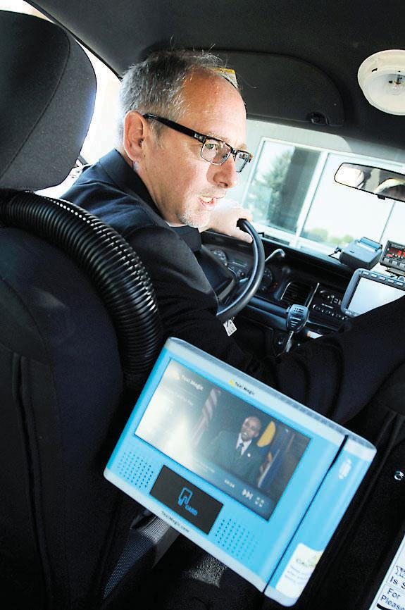 Randy Jensen, general manager at Yellow Cab, sits behind the wheel of a taxi equipped with a monitor that shows a Visit Denver video to passengers.