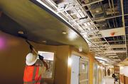 A worker paints the ceiling at the new addition of the University of Colorado Hospital. Haselden Construction is ahead of schedule for completing the project.