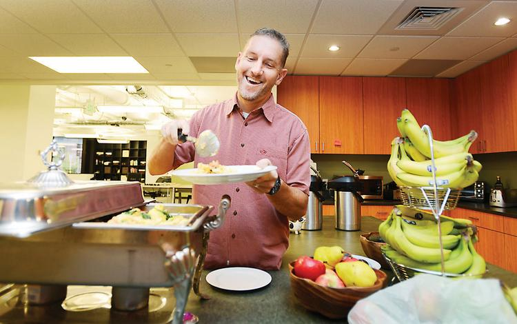 Greg Greenstreet, vice president of engineering at Gnip in Boulder, fills his plate with the free breakfast that's offered every day — just one of many company perks.