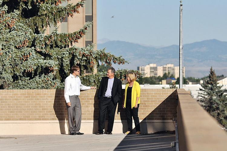 Jeff Carlson, project manager at Omni Development Corp.; Dennis Witte, owner of Omni Development Corp.; and Gayle Jetchick, executive director of the Havana Business Improvement District, meet on the third floor deck at 1470 S. Havana St. The building is slated to be senior housing.