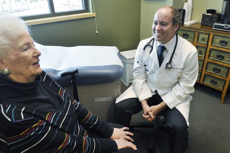 Dr. Charles Miranda talks with one of his patients, Claire MacGregor, at his South Denver Internal Medicine office near Sky Ridge Medical Center. Miranda offers concierge medicine, also called direct primary care.