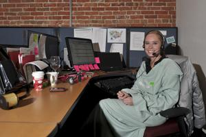 Briana Patterson of ReadyTalk sits at her desk with a company Snuggie on. The company gave employees Snuggies for when it's cold in the office.