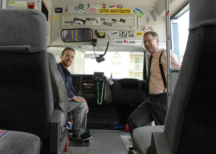 Jeffrey Buxton climbs aboard the Green Mountain Ski Bus, while Andrew Stokes waits in the driver's seat. Buxton is president of the ski bus company; Stokes is vice president.