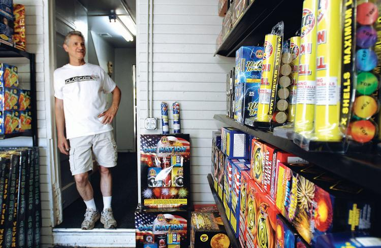 Brent Hinton, manager of Davey Jones Fireworks at West 52nd Avenue and Federal Boulevard, looks over the stock of displays. Brad Witherell, owner of Davey Jones Fireworks, said he expects sales revenue to be 80 to 85 percent lower this year than in 2011 because of the state fire ban.