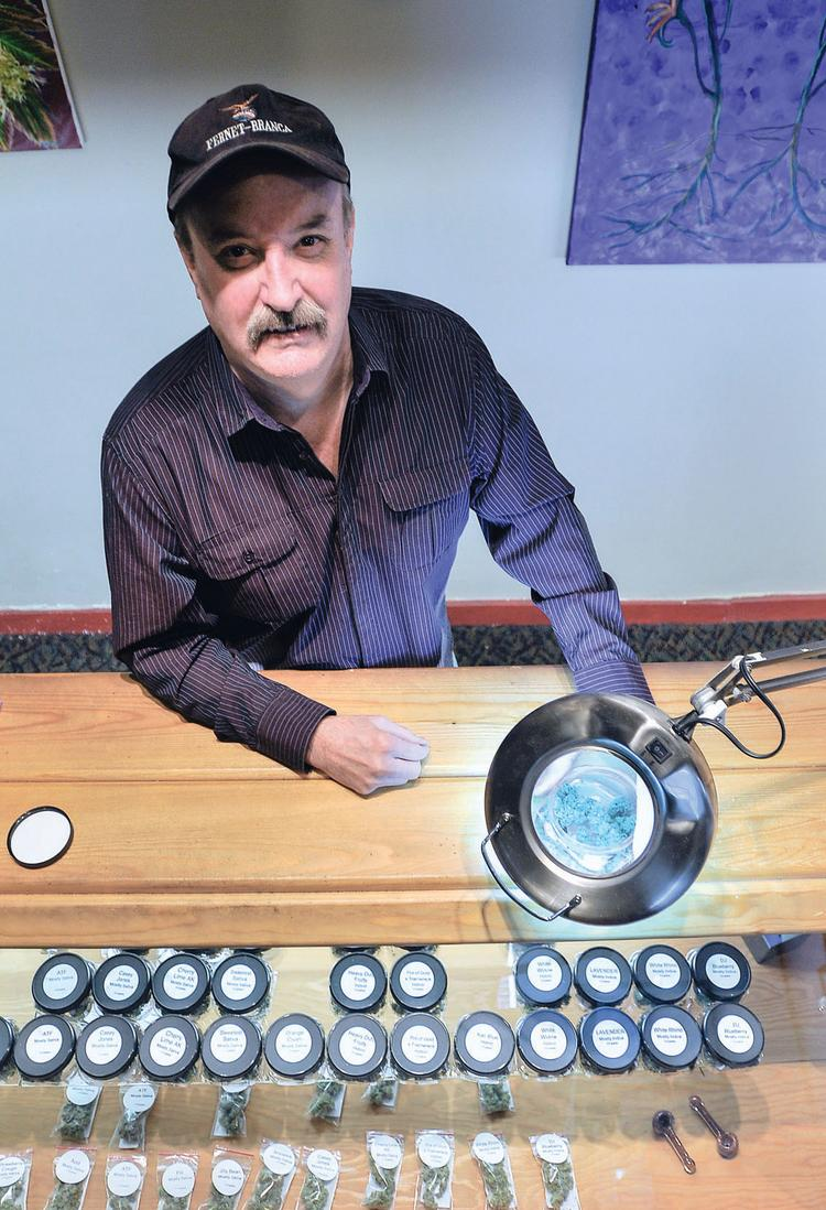Terry Hobbs, an employee at The Kind Room on South Broadway, moves marijuana under a magnifying light. Customers use the light to look for impurities.