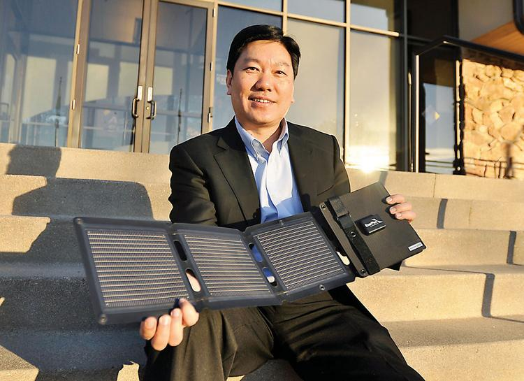 Victor Lee, CEO of Thornton's Ascent Solar Technologies Inc., holds the company's EnerPlex Kickr IV, a flexible solar-power panel capable of charging phones, music players and other small, electronic equipment.