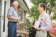 Lang Sias, right, a Republican candidate for Senate District 19, introduces himself to an Arvada resident.