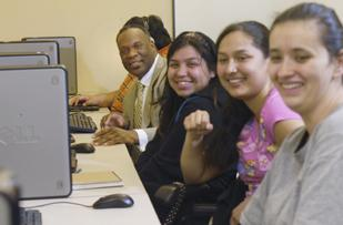 Rich Jennings (left), region vice president at Comcast, sits in on a computer class at Mi Casa Resource Center, a nonprofit that helps Latino and low-income families gain employment. It is one of the company's philanthropic partners.