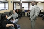 Rich Jennings (right), region vice president at Comcast, talks to students in a computer class at Mi Casa Resource Center. The Comcast Digital Connector program enables participants at Mi Casa to earn Cisco certification in hardware and software.