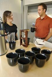 Ping Identity employees Melissa Kaufman, market development, and Brandon Meyers, inside sales, fill up on Costa Rican coffee brought in by their CEO, Andre Durand.