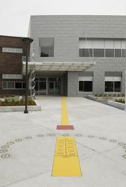The analemmic sundial at the school's main entrance is a more accurate version of the standard sundial, separating the months January to May from the months July to November into separate columns. If a student stands in a location corresponding to the actual date, their shadow will fall precisely on the actual time.