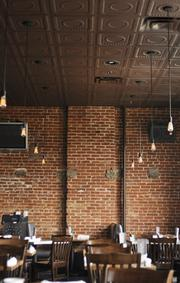 Euclid Hall's two-level modern look features exposed Edison bulbs throughout, schoolhouse chairs, a mix of aluminum and wood tables, tin ceiling and hot rolled steel rails all set against the exposed brick walls of the building, a Larimer Square structure built as a residence in 1883.