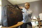 Dominic Martinez, president of MyGoFlight, works with flight bags.