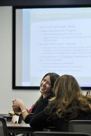 Elizabeth Springer,  manager of business operations and contracting at New West Technologies, chats with a colleague during a staff meeting at the Federal Center. The company landed a multiyear contract with the Department of Energy, which prompted it to add 56 employees, doubling its staff.