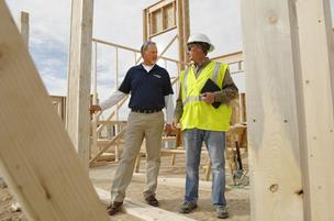 Tom Morton, a senior vice president at Brookfield Residential Colorado, talks with construction manager Jim Sanford at the first home to be built at the Midtown development near West 64th Avenue and Pecos Street.