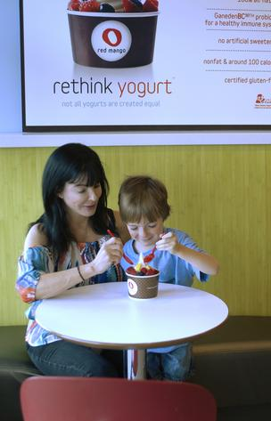 Nikki Lockton, owner of Red Mango in Highlands Ranch, digs into some yogurt and fruit with her son, Stevie, 8.