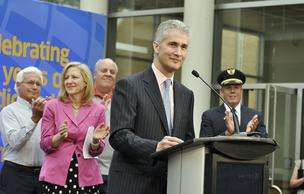 Jeff Smisek, president and CEO of United Airlines, announces a direct flight from Denver International Airport to Tokyo at a press conference May 22. He is joined on stage by Kim Day (in pink), manager of aviation at DIA, and some United employees.