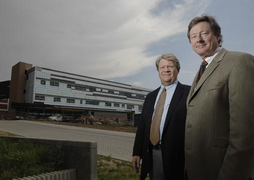 Drew Detamore, director of the Infrastructure and Campus Development Office at NREL, and Jeff Baker, director of the Office of Laboratory Operations at NREL, in front of the group's new building in Golden.