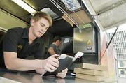 Charlie Parsons, employee at Basic Kneads, a pizza oven truck and caterer, uses Square mobile credit card readers.