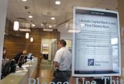 A sign on the door at the Cherry Creek location of Colorado Capital Bank lets customers know that First Citizens Bank is the new owner.