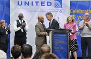 Jeff Smisek, president and CEO of United Airlines (at the podium), is congratulated by Denver Mayor Michael Hancock after announcing the airline's direct flight from DIA to Tokyo at a press conference May 22. They are joined on stage by Kim Day (in pink), manager of aviation at DIA, and some United employees.