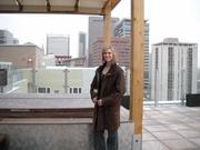 Kelsey Young, leasing and marketing expert at 2020 Lawrence., stands in front of the roof-top hot tub.