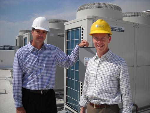 Chris Achenbach, principal (left), and David Zucker, development manager, of Zócalo, in front of variable refrigerant flow units. The units are expected to save residents of some new downtown Denver apartments 40 percent on their heating and cooling bills.
