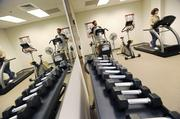 Oakwood Homes' Aaron Williams, purchasing agent, and Danielle Wegman, closing coordinator, work out in the onsite gym.