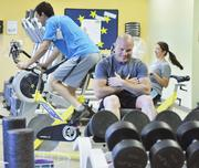Kevin Tolley, James Vardas and Susan Francis work out at Amgen's fitness center in Longmont.