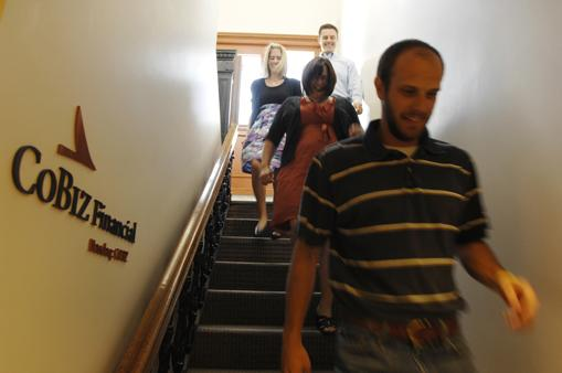 CoBiz Financial employees climb stairs as part of their exercise plan. Taking to the stairs here are, from top left, Laura Galligan, insurance business analyst; L. D. Randle, senior internal auditor; Sarah Saltzman, HR support services specialist; and Kyle Clark, staff auditor.