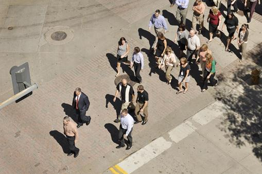 Bob Reiter, president at IMA, (at front of group) and Rob Cohen, chairman and CEO, (behind him in red tie) lead a walk with company employees in LoDo.