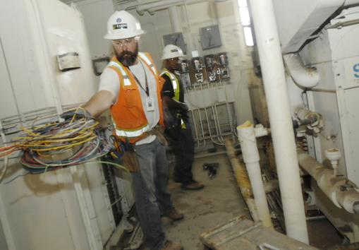 Josh Kylander, foreman, and Tedros Habteslassie, fourth-year apprentice, with E Light Electric Services, work a job at Presbyterian St. Luke's Hospital.