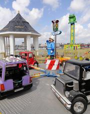 Two of the rides for younger children (36 inches tall minimum): the Big Wheelin' truck convoy, foreground, and the Frog Hopper, shown in background, a 22-foot suspension drop ride. The third ride for small children is the Texas Tea spinning teacups ride. A separate building will house a pair of bumper car rides — one for kids and one for adults.
