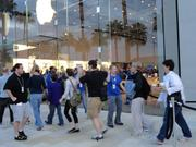 Apple employees energized the crowd before the store's opening and high-fived customers as they entered the store.
